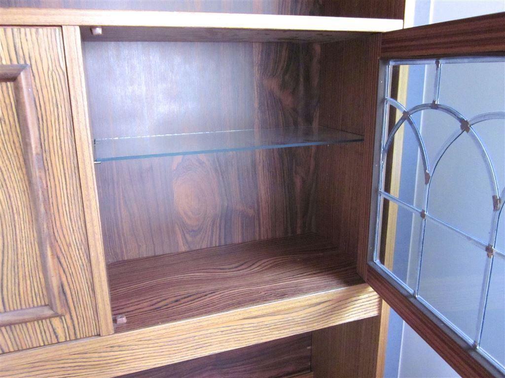 Äldre bokhylla i brun randigt trä med vackra detaljer   belysning