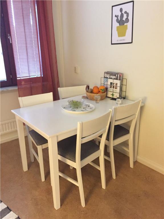 Vitt köksbord och 4 tillhörande köksstolar med gråa dynor på ...