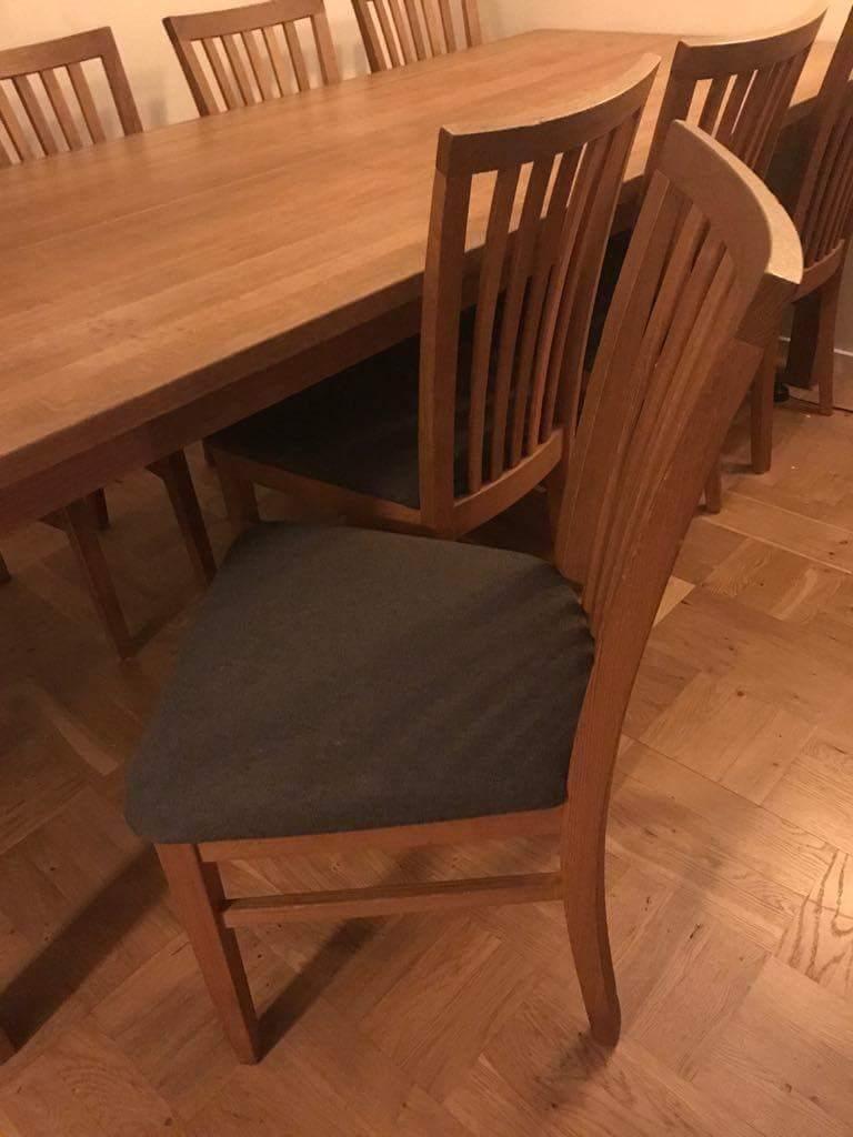 Stort matbord i massiv ek samt 12 stolar i ek med grå tygsits på