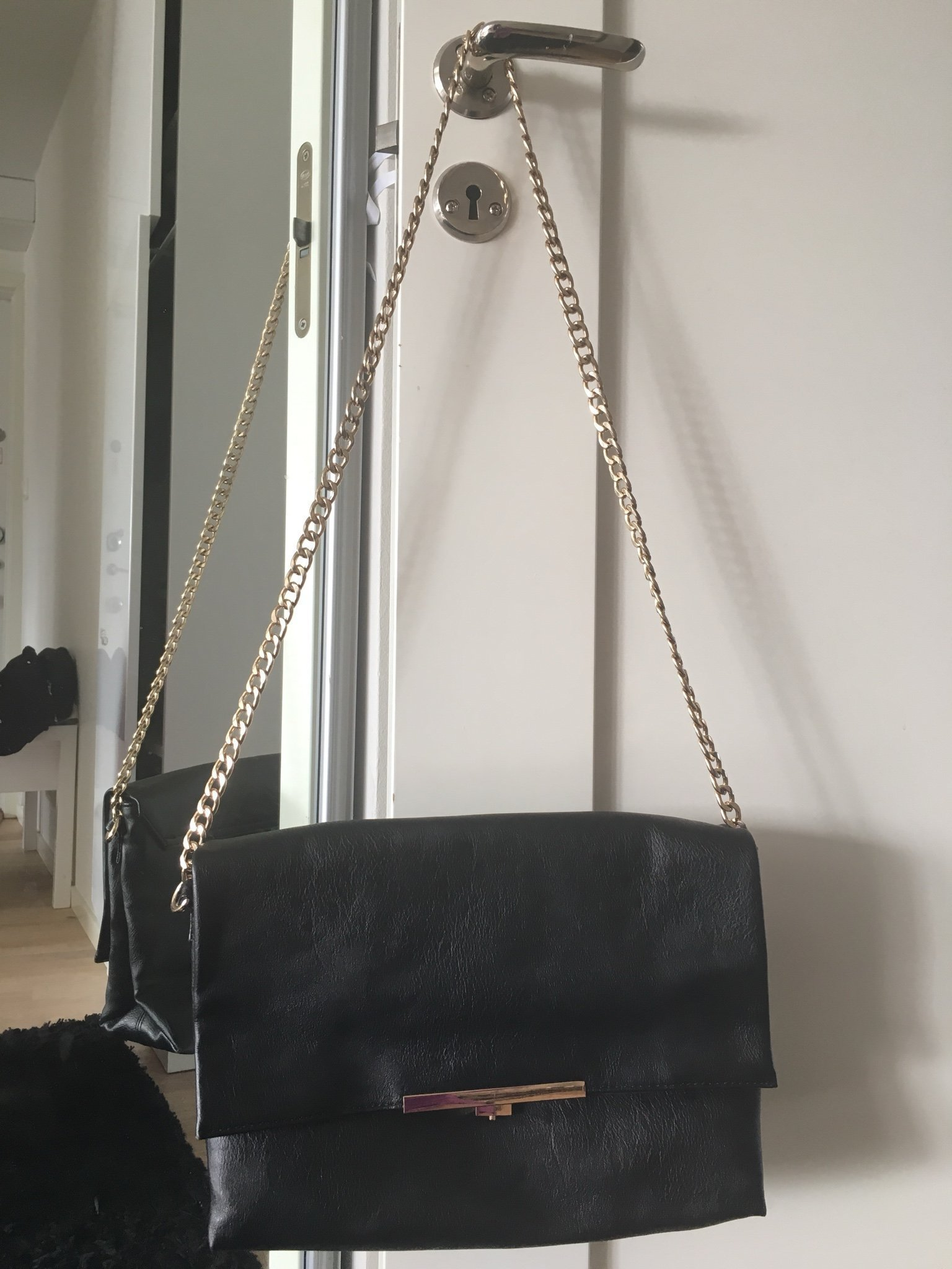 svart handväska med gulddetaljer