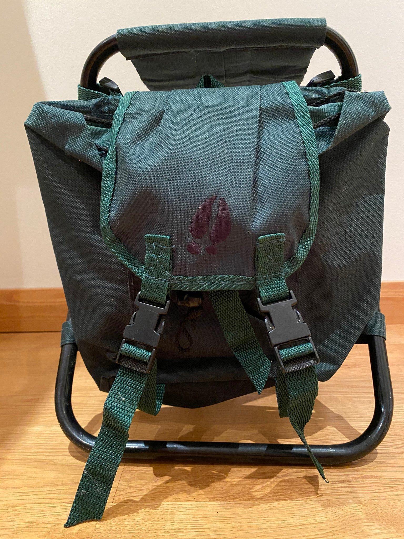 Grön ryggsäck med svarta detaljer med stol för barn