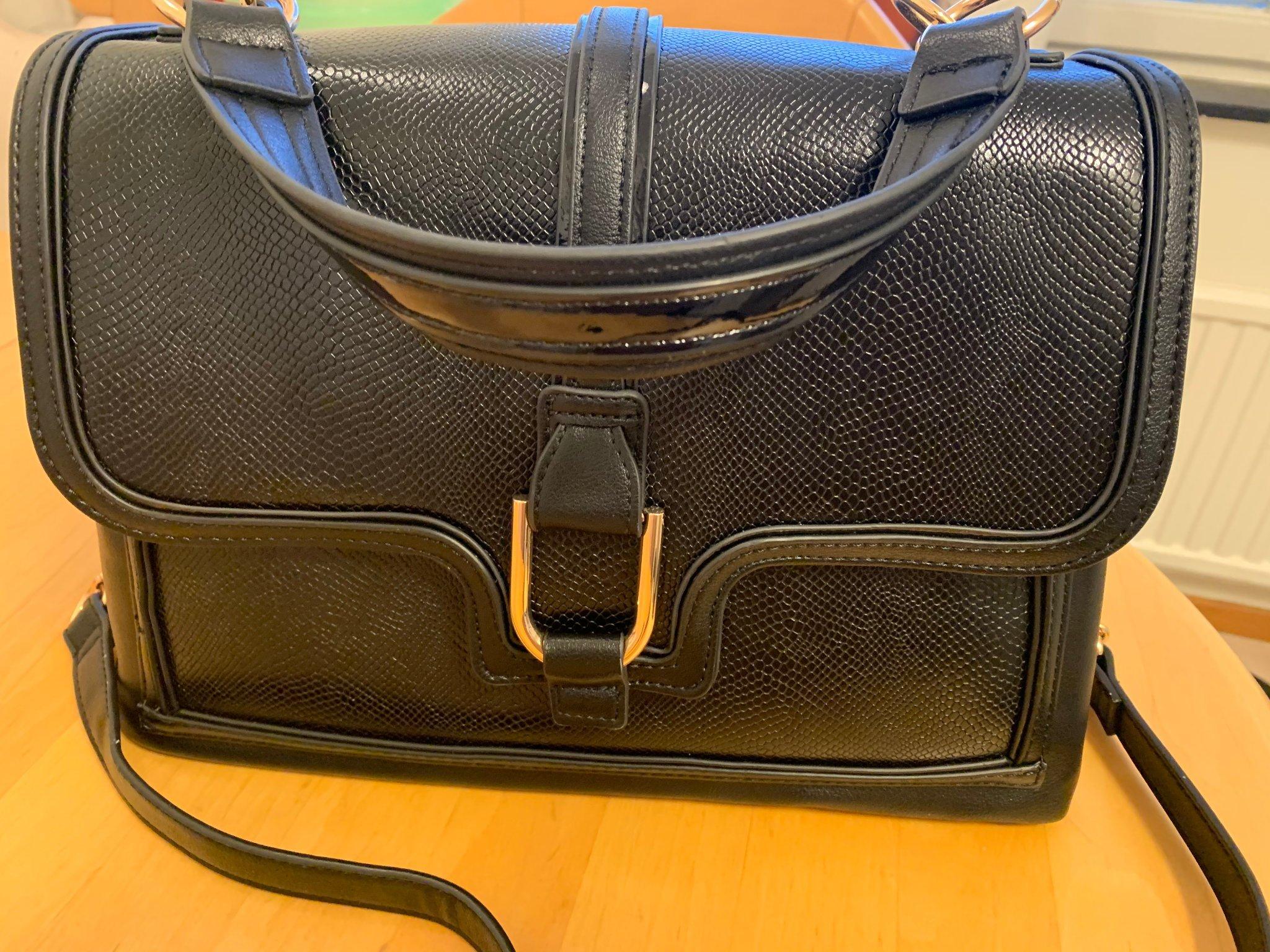 en svart medel stor handbagage väska