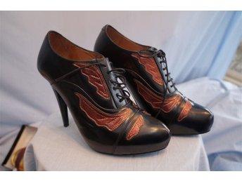 Javascript är inaktiverat. - Norrtälje - Exklusiva Designade Italienska Boots med stilett klack 11,5 cm, patenterat läder, handgjorda, Svarta med kopparfärgade inslag. Tillverkade i Portugal. Finns i liten upplaga. Märke Minimarket. Storlek 38. Butikspris 2.500 kr. Du finner dess - Norrtälje