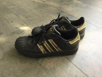 Adidas svarta sneakers med gulddetaljer, storlek 35