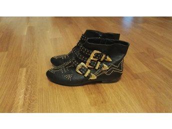 svarta skor med gulddetaljer