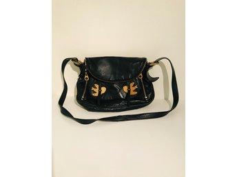 Begagnad svart Michael Kors handväska med axelrem och gulddetaljer