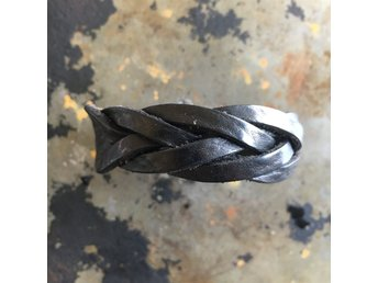 Javascript är inaktiverat. - Sundbyberg - Armband i svart flätat skinn. Längd 22 cm. Silverfärgat spänne. - Sundbyberg
