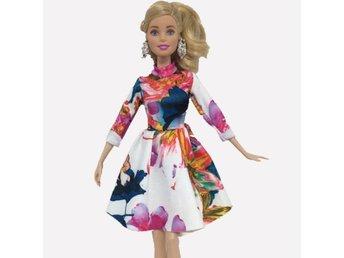 FYND! Ny klänning till Barbie. Storblommig och färgstark klänning.Present? - överlida - Låter bilderns tala. Tyget av syntetisk natur och skrynkelfri. Kommer från rökfritt hem med katt. Samfraktar givetvis. - överlida