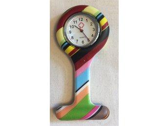 """Javascript är inaktiverat. - Blentarp - Vårdklocka eller sjuksköterskeklocka. """"Quartz"""" Klockan drivs med batteri och sitter i ett silikonskal som färstes med en nål som finns på baksidan. Själva klockan mäter ca 3cm i diameter och med silikonskalet ca 4,2, 4,3 cm längden uppi - Blentarp"""